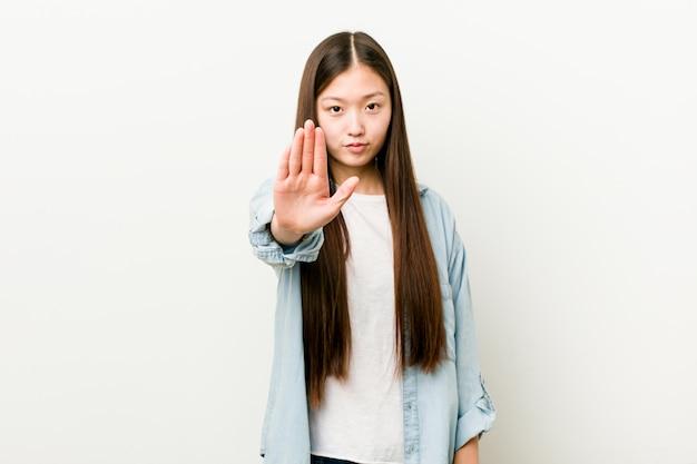Mujer asiática joven que se coloca con la mano extendida que muestra la señal de stop, previniéndole.