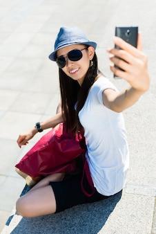 Mujer asiática joven que hace cuadros del selfie