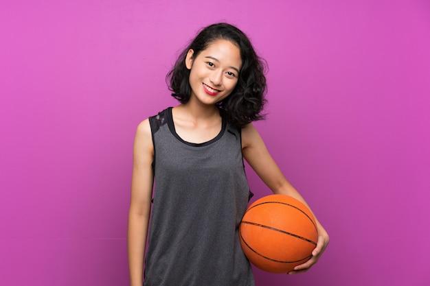 Mujer asiática joven que juega a baloncesto sobre la pared púrpura aislada