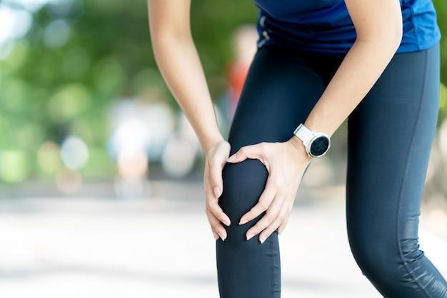 Mujer asiática joven que lleva a cabo dolor de la rodilla en parque de naturaleza público corriente