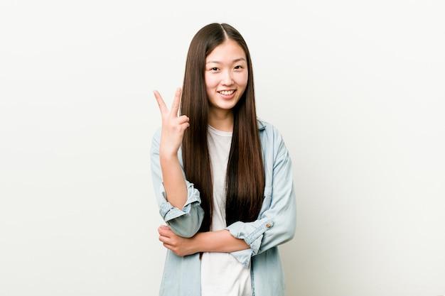 Mujer asiática joven que muestra el número dos con los dedos.
