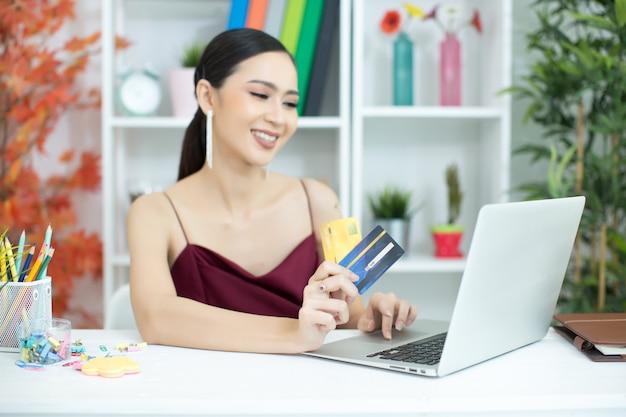 Mujer asiática joven que paga con la tarjeta de crédito