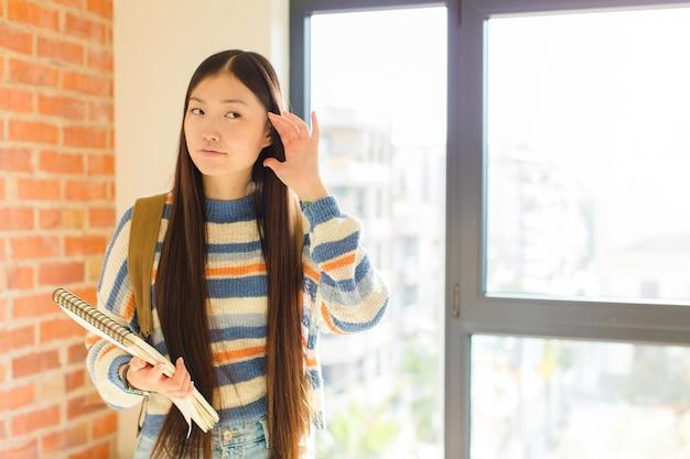 Mujer asiática joven que parece seria y curiosa, escuchando, tratando de escuchar una conversación secreta o chismes, escuchando a escondidas