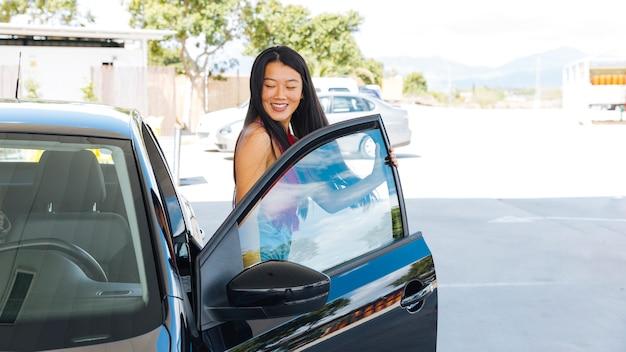 Mujer asiática joven que sale del coche en la gasolinera