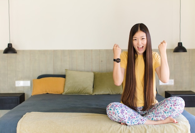 Mujer asiática joven que se siente feliz, positiva y exitosa, celebrando la victoria, los logros o la buena suerte