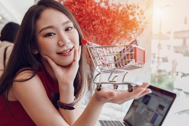 Mujer asiática joven que sonríe sosteniendo el carro de la compra y la tarjeta de crédito en manos mientras que feliz se relaja en cafetería