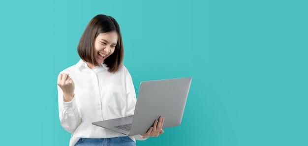 Mujer asiática joven que sonríe sosteniendo el ordenador portátil con la mano del puño y emocionada para el éxito.