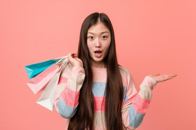 La mujer asiática joven que sostenía un bolso de compras impresionó llevar a cabo el espacio de la copia en la palma.