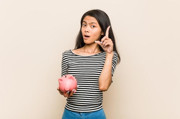 Mujer asiática joven que sostiene una batería guarra que tiene una gran idea, concepto de creatividad.