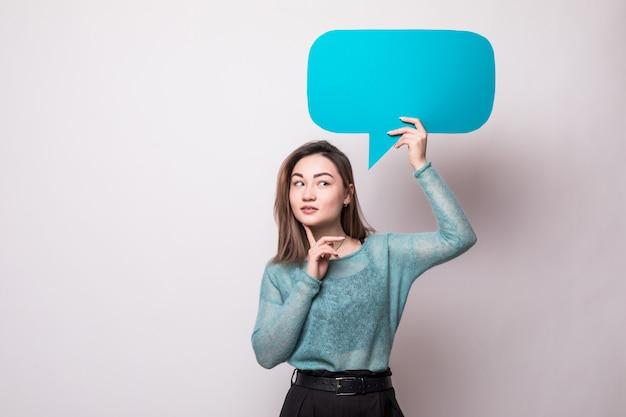 Mujer asiática joven que sostiene la burbuja del discurso aislada en la pared blanca