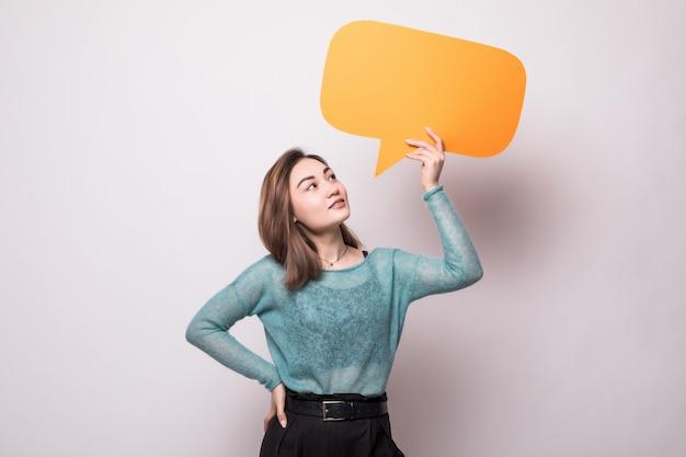 Mujer asiática joven que sostiene la burbuja del discurso aislada en la pared