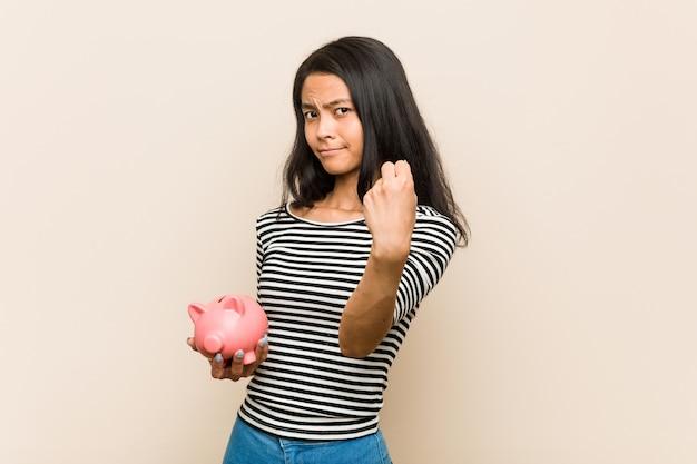 Mujer asiática joven que sostiene una hucha que muestra el puño a la cámara, expresión facial agresiva.