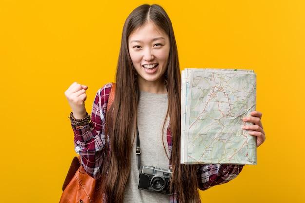 Mujer asiática joven que sostiene un mapa que anima despreocupado y emocionado. concepto de victoria