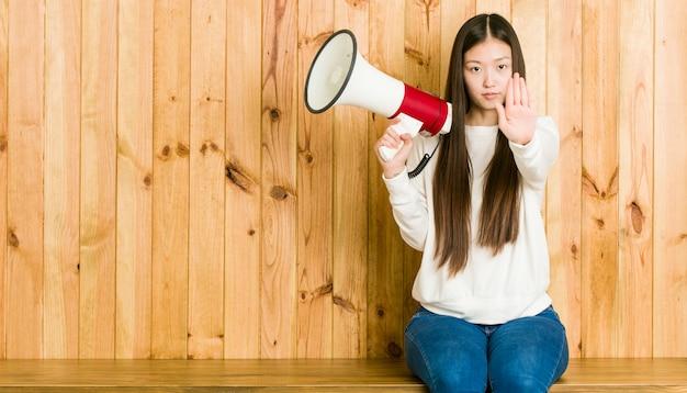 Mujer asiática joven que sostiene un megáfono que se coloca con la mano extendida que muestra la señal de stop, previniéndole.