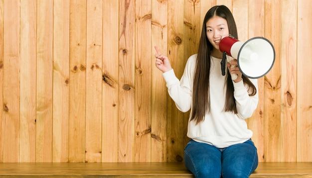 Mujer asiática joven que sostiene un megáfono que sonríe alegremente que señala con el índice lejos.