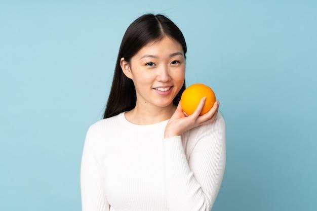 Mujer asiática joven que sostiene una naranja sobre la pared azul aislada
