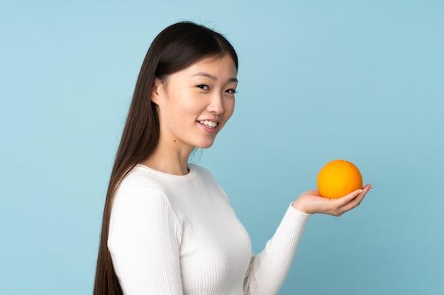 Mujer asiática joven que sostiene una naranja sobre la pared azul