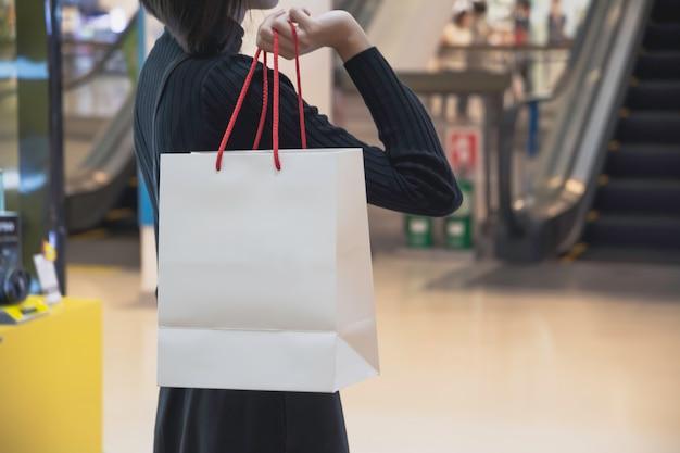 Mujer asiática joven que sostiene el panier en alameda de compras. concepto de compra