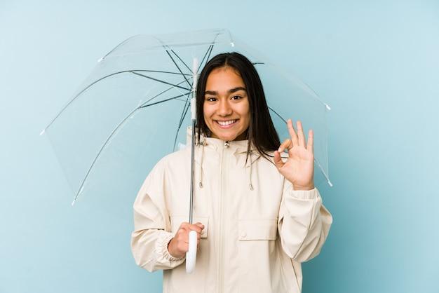 Mujer asiática joven que sostiene un paraguas alegre y confiado que muestra el gesto aceptable.