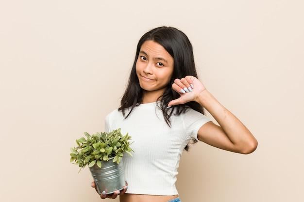 Mujer asiática joven que sostiene una planta que muestra un gesto de la aversión, pulgares abajo.