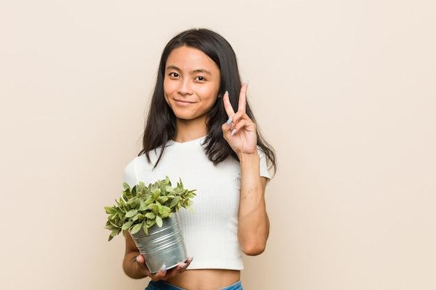 Mujer asiática joven que sostiene una planta que muestra el número dos con los dedos.