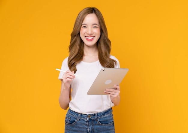 Mujer asiática joven que sostiene la tableta digital y que sonríe con el tacto en la pantalla, fondo amarillo claro.