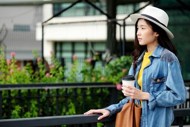 Mujer asiática joven que sostiene una taza de café de papel para llevar mientras que se coloca al aire libre fondo de la ciudad