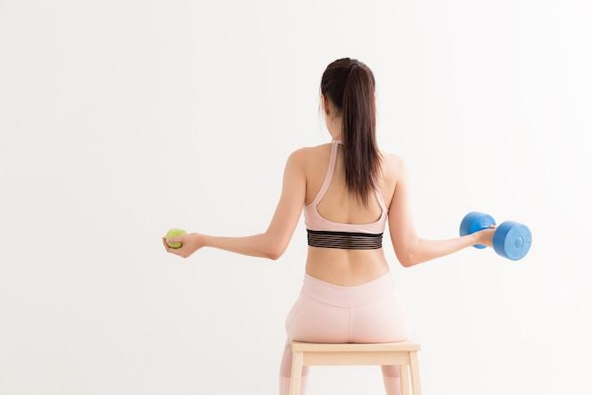 Mujer asiática joven que sostiene una pesa de gimnasia y manzana en el fondo blanco, estilos de vida sanos concentrados