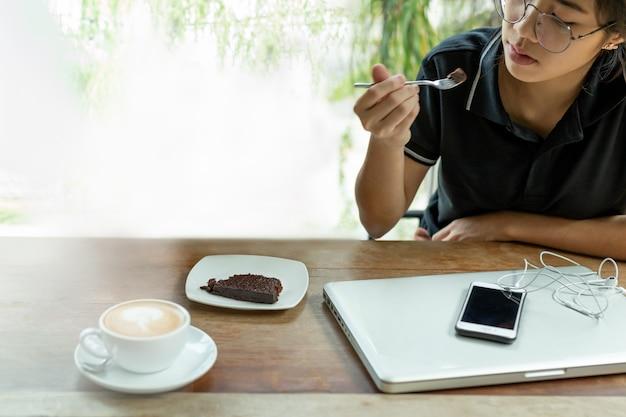 La mujer asiática joven que tenía descanso para tomar café con la torta del brownie en café seleccionó el foco.