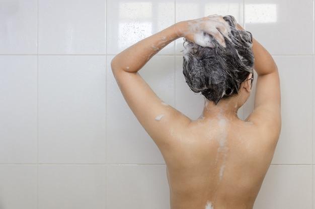 Mujer asiática joven que toma una ducha y que lava el pelo en el cuarto de baño blanco