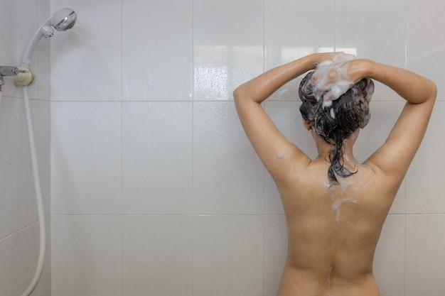 Mujer asiática joven que toma una ducha y que lava el pelo debajo de caliente