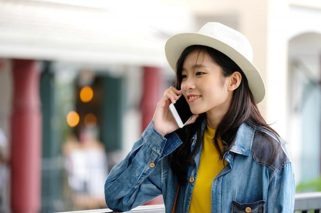 Mujer asiática joven que toma el teléfono en la ciudad al aire libre, gente en el teléfono en formas de vida urbanas
