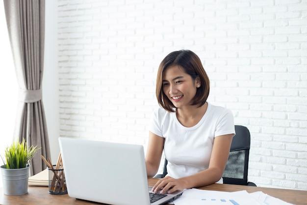 Mujer asiática joven que trabaja en la computadora portátil