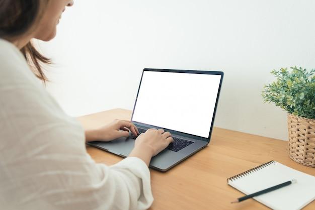 Mujer asiática joven que trabaja usando y escribiendo en la computadora portátil con mock up pantalla en blanco en blanco