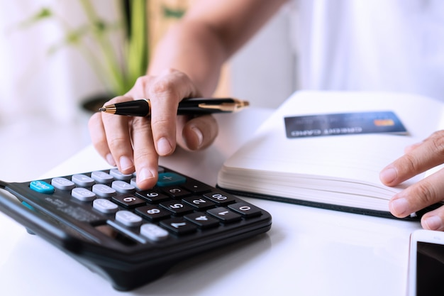 Mujer asiática joven que usa la calculadora con la tarjeta de crédito, el teléfono inteligente y el cuaderno en el escritorio en la sala de estar. trabajar desde casa concepto.