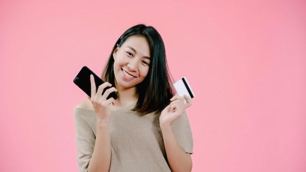 Mujer asiática joven que usa las compras en línea de compra del smartphone por la tarjeta de crédito que siente la sonrisa feliz en ropa informal sobre tiro rosado del estudio del fondo.