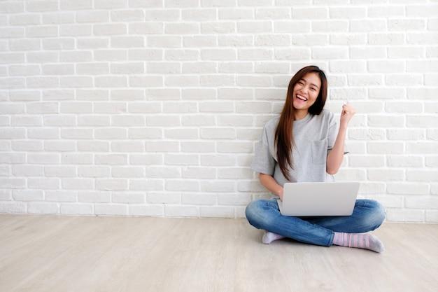 Mujer asiática joven que usa la computadora portátil que se sienta delante de la pared de ladrillo blanca