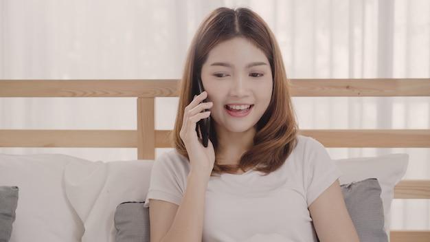 La mujer asiática joven que usa smartphone mientras que miente en cama después de despierta por la mañana