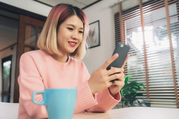 Mujer asiática joven que usa smartphone mientras que miente en el escritorio en su sala de estar