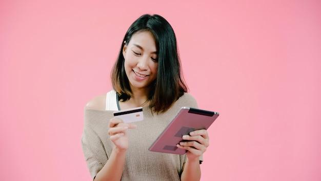 Mujer asiática joven que usa la tableta que compra compras en línea por la tarjeta de crédito que siente la sonrisa feliz en ropa informal sobre tiro rosado del estudio del fondo. la mujer alegre adorable sonriente feliz disfruta de éxito