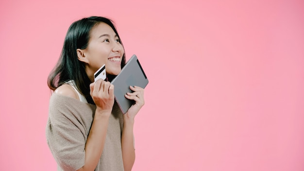 Mujer asiática joven que usa la tableta que compra compras en línea por la tarjeta de crédito que siente la sonrisa feliz en ropa informal sobre tiro rosado del estudio del fondo.