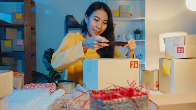 Mujer asiática joven que usa el teléfono inteligente que toma la imagen del código de barras en el producto del paquete para la entrega del envío al cliente