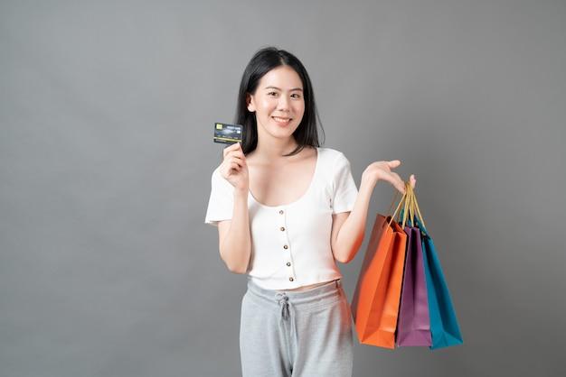 Mujer asiática joven que usa el teléfono con la mano que sostiene el bolso de compras en la pared gris