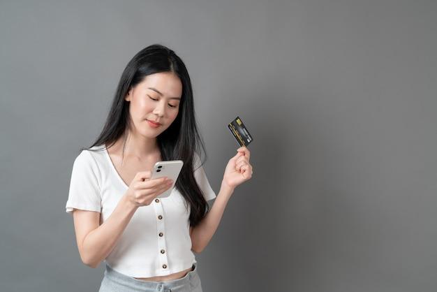 Mujer asiática joven que usa el teléfono con la mano que sostiene la tarjeta de crédito - concepto de compras en línea