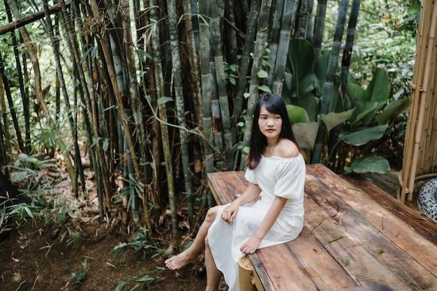 La mujer asiática joven se relaja en el bosque, el utilizar femenino hermoso feliz relaja tiempo en naturaleza.