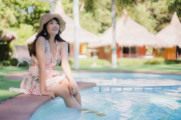 La mujer asiática joven se relaja cerca de piscina en el hotel, feliz femenino hermoso se relaja cerca del mar.