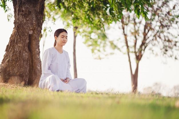 La mujer asiática joven relaja la meditación blanca del vestido que lleva en los campos de hierba verde