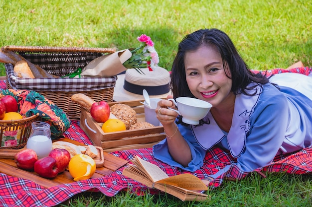 La mujer asiática joven relaja tiempo en park.she está bebiendo té y está mintiendo en la hierba al lado de picn