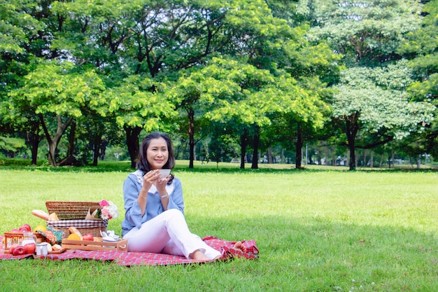 La mujer asiática joven relaja tiempo en parque por la mañana ella está tomando té.