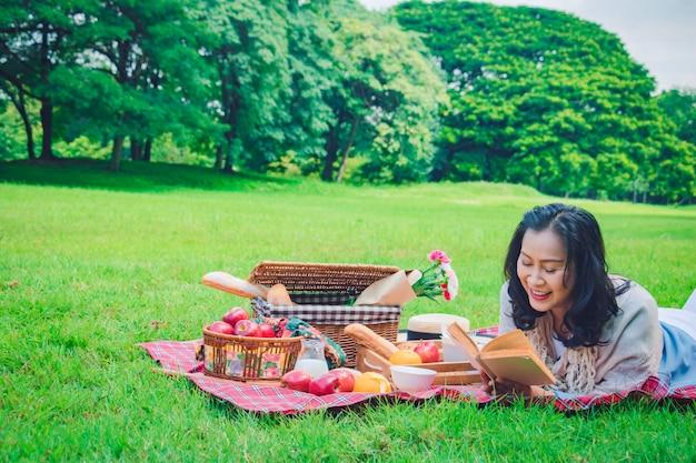 La mujer asiática joven relaja tiempo en parque